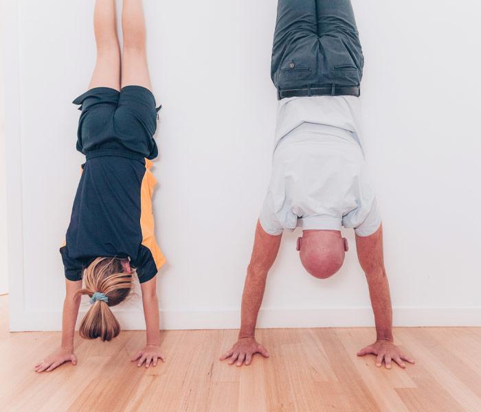 John Meade and teenage girl doing handstand