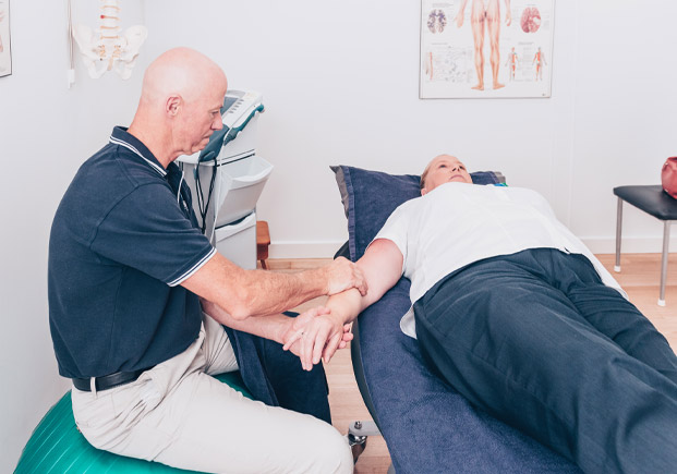 John Meade performing physiotherapy treatment on patient