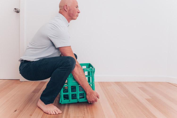 Man lifting a green box with correct posture