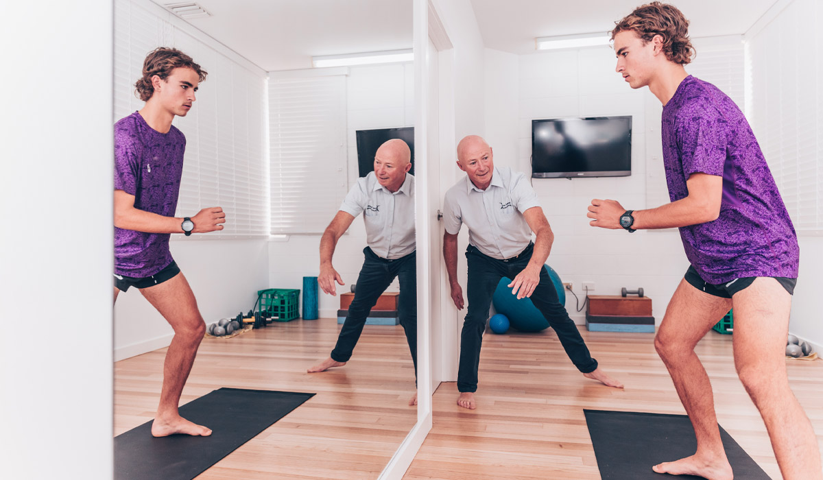 John Meade providing movement training session with male patient